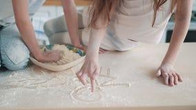 As mãos ascendentes próximas da menina tiram o sorriso pouco homem da farinha branca na tabela, movimento lento