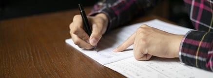 As mãos ascendentes próximas do estudante escrevem para baixo notas da música na classe na escola f fotografia de stock