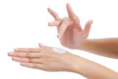 As mãos asiáticas da mulher da beleza aplicam a loção e o creme em sua mão Imagem de Stock
