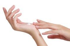 As mãos asiáticas da mulher da beleza aplicam a loção e o creme em sua mão Foto de Stock
