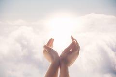 As mãos aumentaram acima em um fundo do céu azul Fotografia de Stock Royalty Free