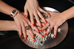 As mãos bonitas da mulher com o polimento vermelho do teste padrão manicured pregam Fotos de Stock Royalty Free