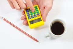 As mãos calculam usando uma calculadora de bolso no fundo branco imagem de stock