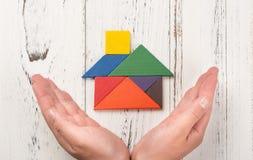 As mãos cercam uma casa de madeira feita o conceito do seguro da casa do tangram ou pela representação do navio do proprietário d fotografia de stock royalty free