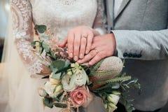 As mãos com anéis dos noivos estão encontrando-se no close-up do ramalhete imagem de stock