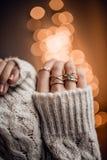 As mãos com anéis luxuosos no bokeh dourado iluminam o fundo Fotografia de Stock
