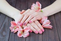 As mãos com cor cor-de-rosa pregam o tratamento de mãos foto de stock