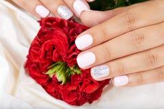 As mãos com os pregos manicured curtos e a rosa do vermelho florescem Fotografia de Stock Royalty Free