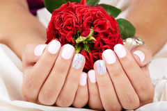 As mãos com os pregos manicured curtos que guardam uma rosa vermelha florescem fotos de stock royalty free