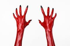 As mãos com pregos pretos, mãos vermelhas de Satã, tema de diabo vermelho de Dia das Bruxas, em um fundo branco, isolado imagem de stock royalty free