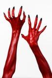 As mãos com pregos pretos, mãos vermelhas de Satã, tema de diabo vermelho de Dia das Bruxas, em um fundo branco, isolado Fotos de Stock