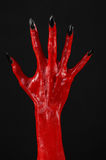 As mãos com pregos pretos, mãos vermelhas de Satã, tema de diabo vermelho de Dia das Bruxas, em um fundo preto, isolado Fotos de Stock