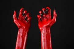 As mãos com pregos pretos, mãos vermelhas de Satã, tema de diabo vermelho de Dia das Bruxas, em um fundo preto, isolado fotografia de stock