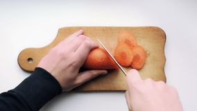 As mãos com uma faca estão cortando cenouras Fatias da cenoura em cozinhar a placa Precisão e precisão Vista superior filme