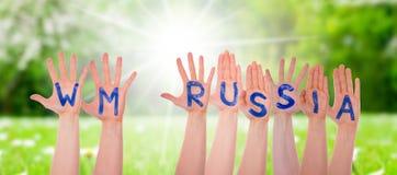 As mãos com WM Rússia significam Rússia 2018, Sunny Grass Meadow Imagens de Stock Royalty Free