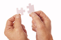 As mãos conectam partes do enigma de serra de vaivém Imagens de Stock