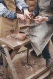 As mãos da ajuda do oleiro fazem o jarro na roda da cerâmica Imagens de Stock Royalty Free