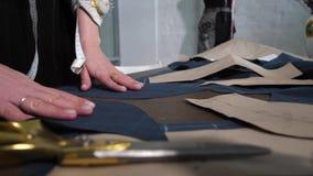 As mãos da costureira que apresentam testes padrões na tabela vídeos de arquivo