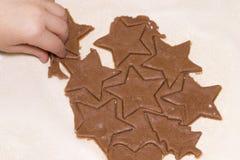 As mãos da criança cortaram a cookie da massa crua em uma tabela de madeira Natal Imagem de Stock Royalty Free