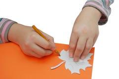 As mãos da criança desenham uma folha com lápis e estêncil Imagens de Stock Royalty Free
