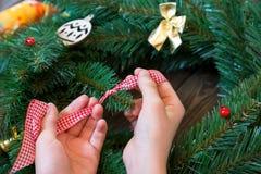 As mãos da criança guardam a fita vermelha e branca para a decoração da grinalda do Natal imagens de stock