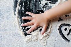 As mãos da criança na farinha Imagens de Stock
