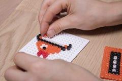 As mãos da criança pequena fazem a arte dos grânulos na forma de um peixe imagem de stock