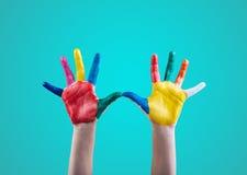 As mãos da criança pintadas com pinturas coloridos do dedo Imagens de Stock Royalty Free