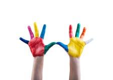 As mãos da criança pintadas com pinturas coloridos do dedo Fotografia de Stock