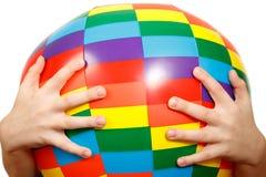 As mãos da criança prendem a esfera inflável grande Fotografia de Stock Royalty Free