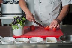 as mãos da faca do cozinheiro chefe cortaram vegetais na placa Imagem de Stock Royalty Free