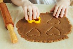 As mãos da jovem criança estão preparando a massa, cozem cookies na cozinha Conceito ascendente próximo do leasure da família imagens de stock