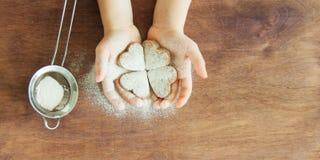 As mãos da jovem criança estão preparando a massa, cozem cookies na cozinha Conceito ascendente próximo do leasure da família imagem de stock