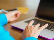 As mãos da jovem mulher bonita que guardam um cartão de crédito e que usam o laptop Imagens de Stock