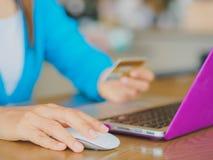 As mãos da jovem mulher bonita que guardam um cartão de crédito e que usam a tabuleta, o smartphone e o laptop Imagem de Stock