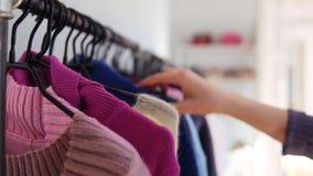 As mãos da jovem mulher com manicurerun na moda através de uma cremalheira da roupa, consultando em um boutique As mãos da mulher filme