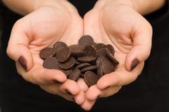 As mãos da jovem mulher em uma forma do coração com chocolate escuro imagens de stock