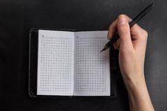 as mãos da jovem mulher guardam páginas abertas do caderno com corrigem na tabela de madeira clara com marcador Fotografia de Stock