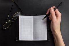 as mãos da jovem mulher guardam páginas abertas do caderno com corrigem na tabela de madeira clara com marcador Imagens de Stock
