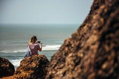 As mãos da jovem mulher usam o smartphone que faz a foto e o vídeo que sentam-se em uma rocha que aprecia a praia imagens de stock