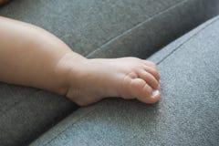 As mãos da mãe e os pés do bebê em um sofá cinzento fotos de stock royalty free