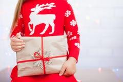 As mãos da menina estão guardando o presente do Natal fotografia de stock