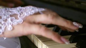 As mãos da menina nas luvas brancas com um tratamento de mãos bonito jogam o piano Jogue a melodia nas notas Ind?stria musical vídeos de arquivo