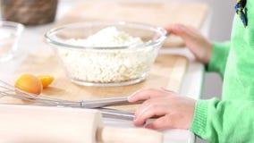 As mãos da menina preparam-se para cozinhar panquecas do requeijão em cozinhar o estúdio vídeos de arquivo