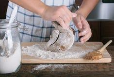 As mãos da menina que amassam a massa para o pão-de-espécie foto de stock royalty free