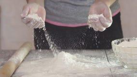 As mãos da menina que aplaudem suas mãos encheram-se com a farinha, filme