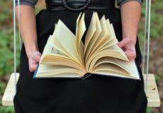 As mãos da menina que giram as páginas do livro foto de stock