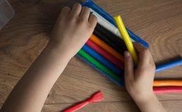 As mãos da menina removem a argila multi-colorida imagem de stock royalty free