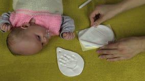 As mãos da mentira e da mãe do bebê preparam o material para a pegada vídeos de arquivo
