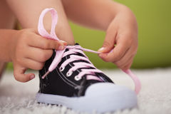 As mãos da moça amarram a profundidade da sapata de campo laço-rasa Foto de Stock